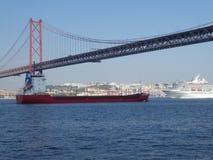 Een rood vrachtschip en een voering onder de brug van 25 April in Lissabon, Portugal, Europa stock foto's