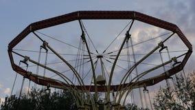 Een roterende carrousel in een pretpark bij zonsondergang stock videobeelden