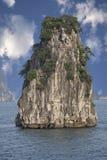 Een rots in het overzees met een blauwe hemel en witte wolken stock fotografie