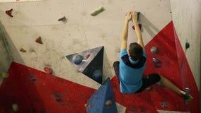 Een rotsklimmer beklimt een steile muur en splitst na een ontbroken poging op om tot de bovenkant te beklimmen stock video