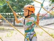 Een rotsklimmer bindt een knoop op een kabel Een persoon treft voor het stijgen voorbereidingen Het kind leert om een knoop te bi Stock Afbeeldingen