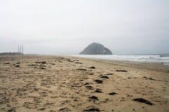 Een rotsklip in de oceaan overdwars van rookstapels Stock Afbeeldingen
