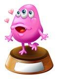 Een roze beaniemonster die zich boven trofeetribune bevinden Royalty-vrije Stock Afbeeldingen