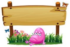 Een roze beaniemonster onder het lege houten uithangbord Stock Afbeelding