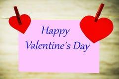 Een roze kaart en twee rode harten die op een koord hangen, dat met rode gespen met de Dag van inschrijvings Gelukkig Valentine w royalty-vrije stock afbeelding