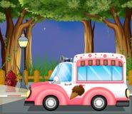 Een roze roomijsauto in de straat Stock Foto