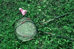 Een roze shuttle en een badmintonracket op het groene gazongras Stock Afbeelding