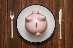 Een roze spaarvarken op schotel Besparingen het concept van de consument Spaarvarken op de plaat met vork en mes Pen, oogglazen e stock fotografie