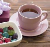 Een roze theekop met schotel, suikergoed, een giftdoos stock fotografie