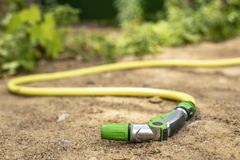 Een rubberslang met een apparaat om vegetatie met water te bespuiten en water te geven ligt op de zandige weg, tegen de achtergro stock afbeelding
