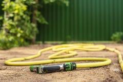 Een rubberslang met een apparaat om vegetatie met water te bespuiten en water te geven ligt op een zandige weg, tegen de achtergr stock fotografie