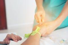 Een rubbertourniquet die wapen het strakke voorbereidingen treffen voor bloeddr. binden Royalty-vrije Stock Fotografie