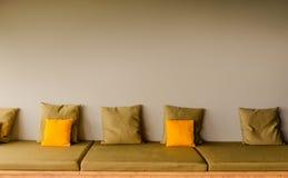 Een rugloze zetelbank met vijf vierkante kaki hoofdkussens en twee heldere gele hoofdkussens De ruimte van het exemplaar stock afbeelding