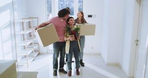 In een ruim huis hebben het charismatische paar en hun vrienden een bewegende gelukkig en opgewekte dag zij die de dozen dragen e stock videobeelden