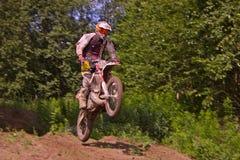 Een ruiter van de sportfiets springt springplank Stock Fotografie