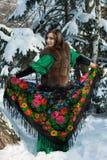 Een Russische schoonheid kleedde zich in sarafan, een bontjas en een Rus Royalty-vrije Stock Afbeelding