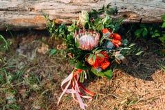 Een rustiek huwelijksboeket met roze linten dichtbij het logboek Stock Afbeeldingen