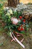 Een rustiek huwelijksboeket met roze linten dichtbij het logboek Royalty-vrije Stock Afbeelding
