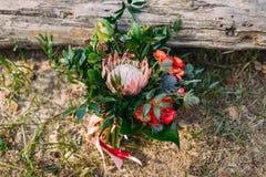 Een rustiek huwelijksboeket met roze linten dichtbij het logboek kunstwerk Stock Fotografie