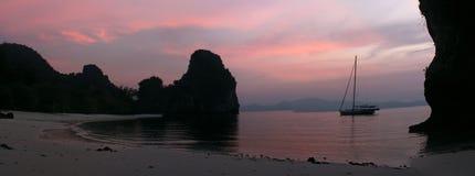 Een sailbot achored voor de kust bij zonsondergang stock foto's