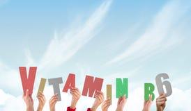 Een Samengesteld beeld die van handen vitamine b6 steunen stock afbeelding
