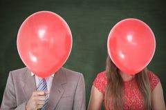 Een Samengesteld beeld van de geeky ballons van de paarholding voor hun gezichten Stock Fotografie