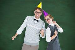 Een Samengesteld beeld van geeky hipsterpaar die een partijhoed dragen Stock Afbeeldingen