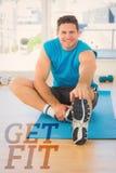 Een Samengesteld beeld van sportieve mens het uitrekken zich hand aan been in geschiktheidsstudio Stock Afbeeldingen