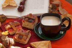 Een a-samenstelling met een kop van melkkoffie, verscheidene stukken eigengemaakte pastei, een geopend boek, kastanjes en droge d Stock Afbeeldingen
