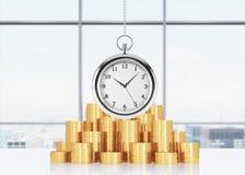 Een samenstelling van gouden muntstukken en het hangen op het kettingszakhorloge Stock Fotografie