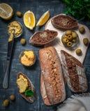 Een samenstelling van twee baguettes van zemelen en gehele korrelbloem Sandwich van hummus en olijven Op het houten uit elkaar pl stock fotografie