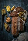 Een samenstelling van twee baguettes van zemelen en gehele korrelbloem Sandwich van hummus en olijven Op het houten uit elkaar pl royalty-vrije stock foto