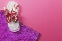 Een sanitair stootkussen bond met lint en vrouwelijke damesslipjes op de roze achtergrond Geneeskunde, vrouwengezondheid en ovula royalty-vrije stock afbeelding