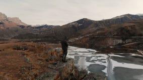 Een satellietbeeld van een mens in een kap bevindt zich op de rand van een klip dichtbij een bergmeer tegen de achtergrond van ep stock videobeelden