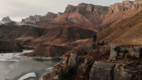 Een satellietbeeld van een mens in een kap bevindt zich op de rand van een klip dichtbij een bergmeer tegen de achtergrond van ep stock footage