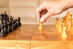 Een schaakpand in een menselijke hand Het begin van het schaakspel T stock afbeeldingen