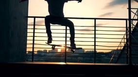 Een schaatser die stunts op een zonsondergangachtergrond doen, langzame motie stock video