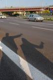 Een schaduw op de weg van Reiswandelaars koppelt het tonen van duimen op straat voor lift tijdens wegreis Gelukkige jongelui royalty-vrije stock foto