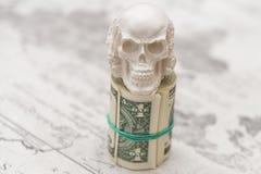 Een schedel die zich op die een bundel van geld bevinden, in een bundel wordt verdraaid royalty-vrije stock foto