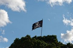 Een schedel en de gekruiste knekels, heel de vlag van Roger vliegen vanaf de bovenkant van een vlagpool royalty-vrije stock foto's