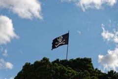 Een schedel en gekruiste knekels, heel de vlag van Roger flys vanaf de bovenkant van een vlagpool royalty-vrije stock afbeeldingen