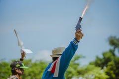 Een scheidsrechter steekt het aanzetpistool voor de agenten van een spoorra in brand stock afbeelding