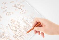 Een schets van de persoonstekening van een stad met ballons en wolken op a royalty-vrije stock foto's