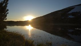 Een schilderachtig meer met een heuvelige bank bij een schitterende zonsondergang in de herfst in slo-mo stock videobeelden