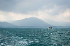 Een schip bij golvende oceaan bij bewolkte ochtend Stock Foto