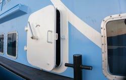 Een schip of een boot broedt deur met de blauwe muur van het kleurenschip op havenmening van uit bodem stock afbeelding