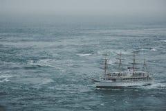 Een schip dat het overzees door een maalstroom kruist Stock Fotografie