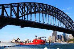 Een Schip die door Sydney Opera House And Harbour-Brug overgaan stock afbeeldingen