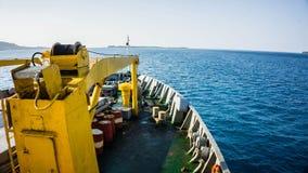 Een schip van voordekmening laadt een benzineolievat in het diepe blauwe overzees van Indonesië royalty-vrije stock fotografie