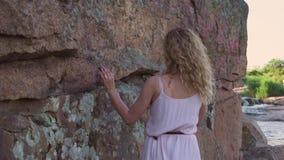 Een schitterend en bevallig meisje in een lange roze kleding loopt langzaam dichtbij een hoge steenrots en raakt het met haar vin stock video